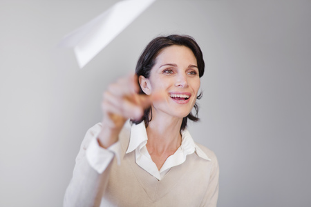 Businesswoman throwing paper airplane