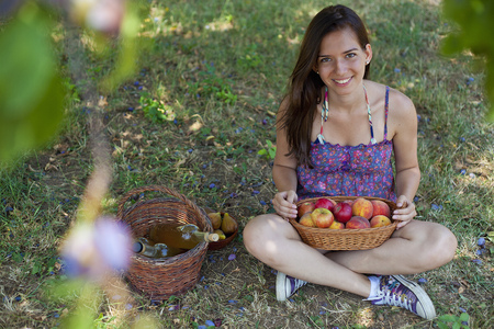 new age: Smiling woman picnicking in orchard LANG_EVOIMAGES
