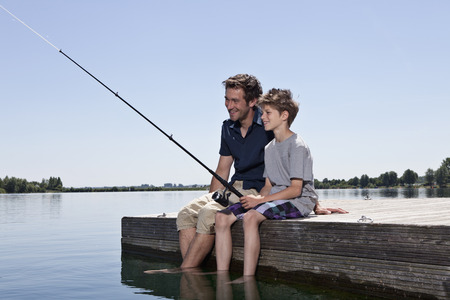 taught man: Father and son fishing together on dock