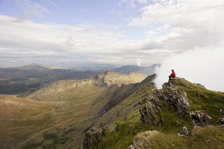wales: Hiker overlooking view from mountaintop