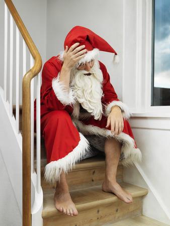 Man in Santa Claus suit sitting on steps