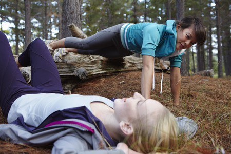 struggled: Women exercising together in forest