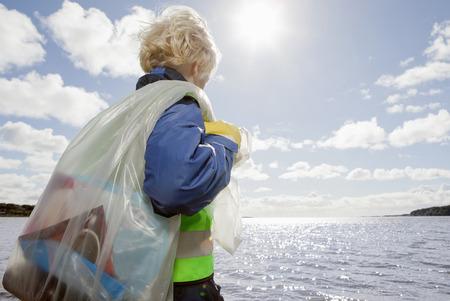 defended: Boy hauling bag of trash on beach