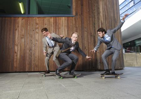 Businessmen riding skateboards LANG_EVOIMAGES