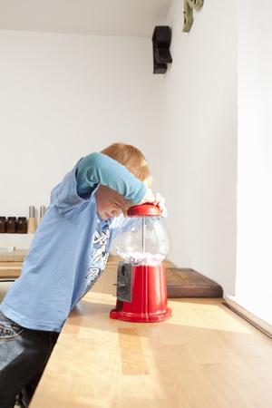 Boy opening gum ball machine in kitchen LANG_EVOIMAGES