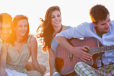 mujeres de espalda: Man playing music for friends on beach LANG_EVOIMAGES