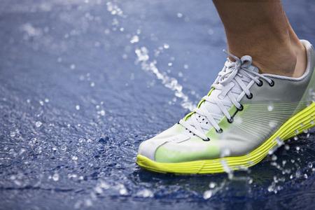 athleticism: Running shoe splashing water on track