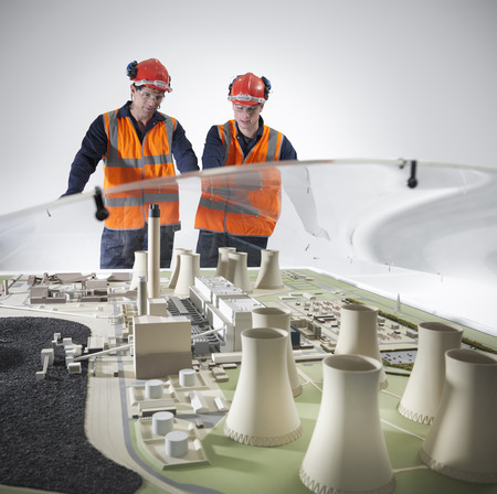 consulted: Workers examining model of power station LANG_EVOIMAGES