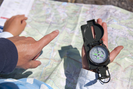 instructs: Father and son using compass and map