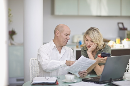 financial planning married: Couple paying their bills at home LANG_EVOIMAGES