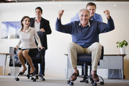 Business people having chair race LANG_EVOIMAGES