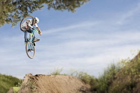 feats: Dirt biker doing tricks during jump