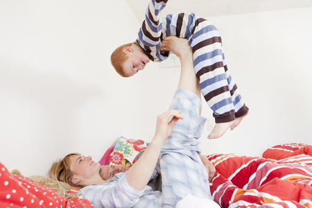 mischievious: Family playing together in bed