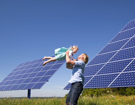 in twos: Father and daughter by solar panels LANG_EVOIMAGES