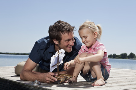 in twos: Father and daughter playing on dock LANG_EVOIMAGES