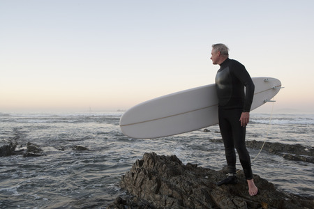 Surfer standing on rocky beach LANG_EVOIMAGES