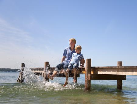 Father and son dangling feet in lake