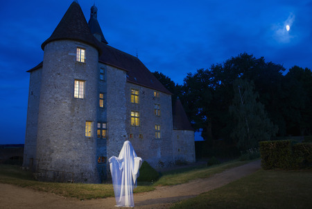 histories: Ghost floating outside stone house