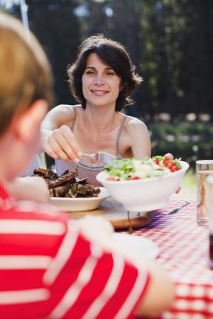 provide: Mother serving salad at picnic LANG_EVOIMAGES