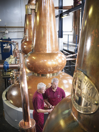consulted: Workers checking stills in distillery