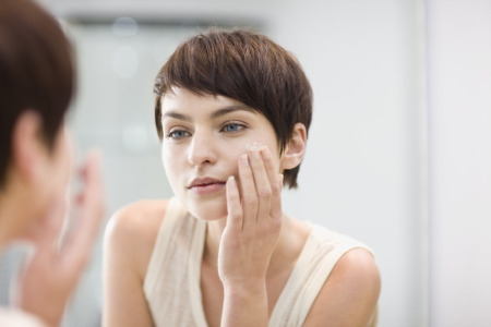 womanly: Woman applying moisturizer in mirror
