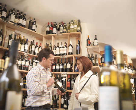 sold small: Wine merchant with customer in shop