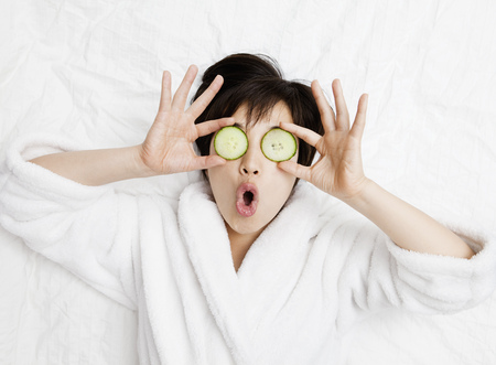 enclose: Woman in bathrobe with cucumbers on eyes