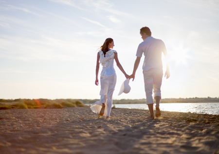 Newlywed couple walking on beach LANG_EVOIMAGES
