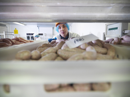 stockmarket: Worker inspecting sausages in factory