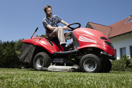 cutted: Man riding lawn mower in backyard LANG_EVOIMAGES