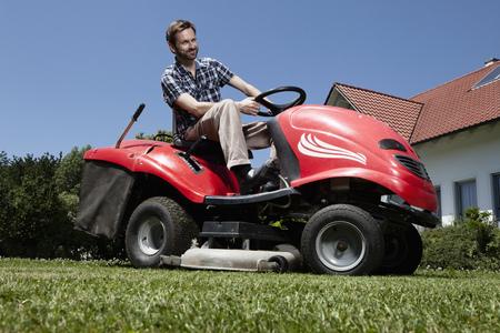 grass cutting: Man riding lawn mower in backyard LANG_EVOIMAGES