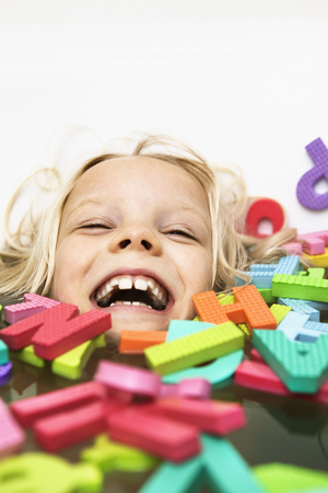submerging: Laughing child playing with foam letters LANG_EVOIMAGES