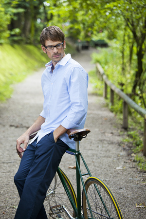 Man leaning on bike on dirt path LANG_EVOIMAGES
