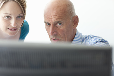 conferring: Business people using computer in office