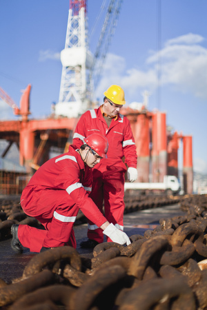 Workers on oil rig examining chains