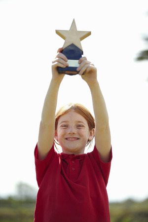 arms lifted up: Girl cheering with trophy outdoors LANG_EVOIMAGES