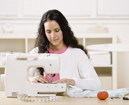 Woman using sewing machine at home LANG_EVOIMAGES