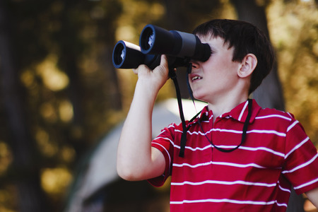 Boy using binoculars at campsite