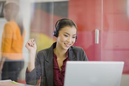 customer service representative: Businesswoman on headset using laptop LANG_EVOIMAGES