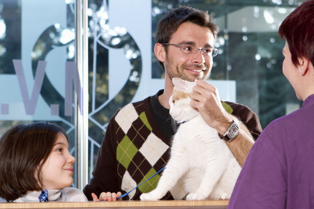 Man with daughter and cat at vet