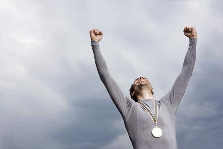 Cheering runner wearing medal LANG_EVOIMAGES