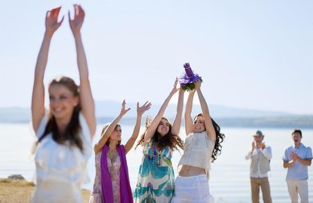 arm bouquet: Women catching bride's bouquet