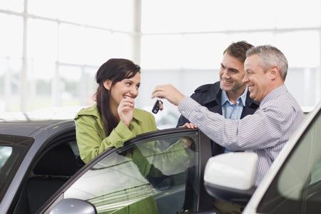 accomplishes: Car salesman giving keys to customer LANG_EVOIMAGES