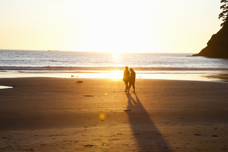 aging american: Couple walking on beach on sunset