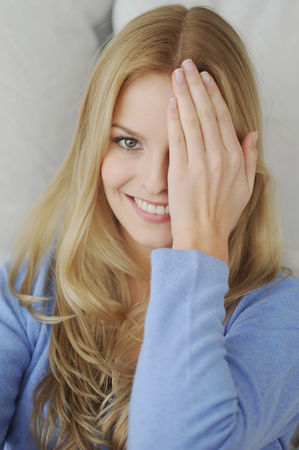 bashfulness: Smiling woman covering one eye