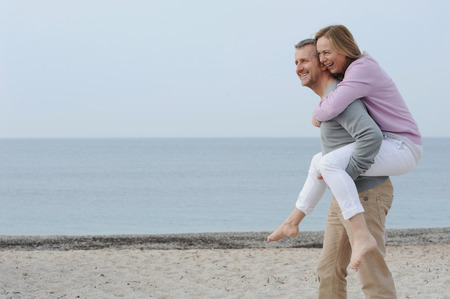 blue waters: Man carrying girlfriend on beach