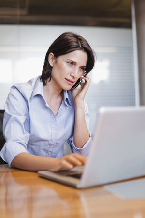 consulted: Businesswoman on cell phone and laptop