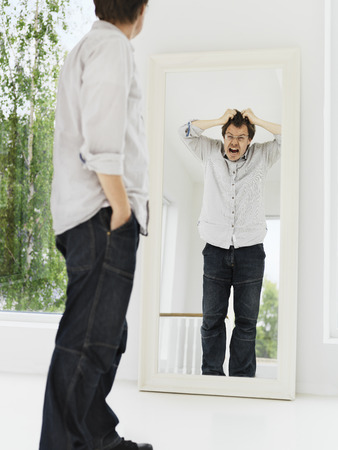 Man examining his grimacing reflection LANG_EVOIMAGES