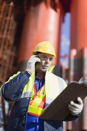 Worker talking on cell phone on oil rig