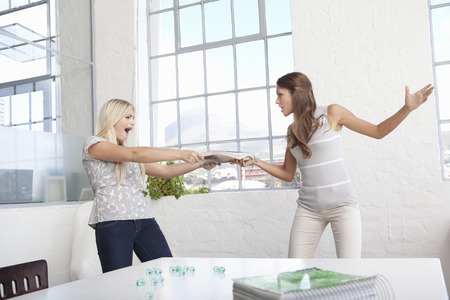 Businesswomen fighting over papers